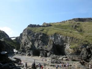 strand met uitzicht op Merlin's Cave en boven de ruïnes